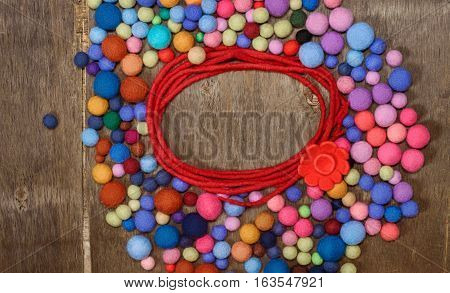 Red circle with flower and multicolored beads made of wool merino on the wooden background. Place for text