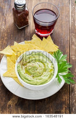 Bowls of hummus and guacamole with tortilla chips. Top view
