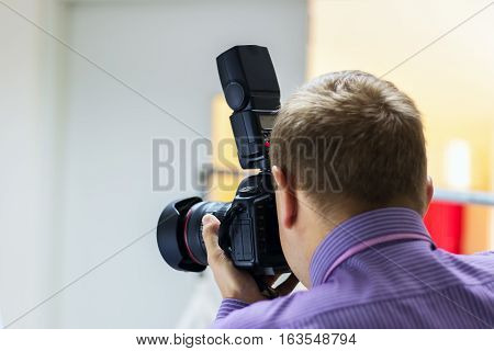 Bend young man taking photo with digital camera side view. stock photo