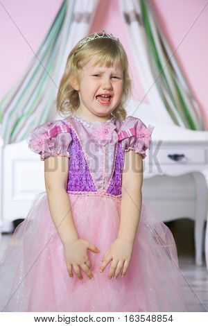 Little unhappy princess girl in pink dress and crown in her royal room is crying.