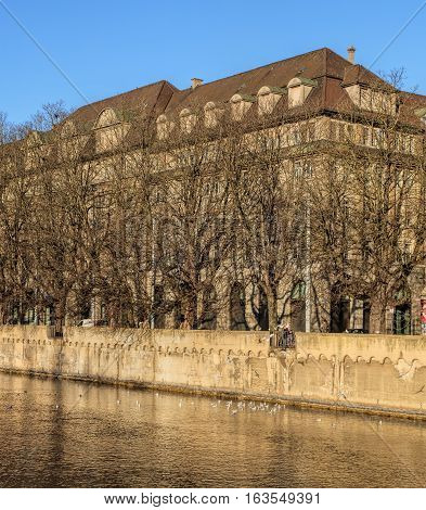 Zurich, Switzerland - 27 December, 2016: the Limmat river trees and buildings along it in wintertime. The Limmat is a river that commences at the outfall of Lake Zurich in the southern part of the city of Zurich.