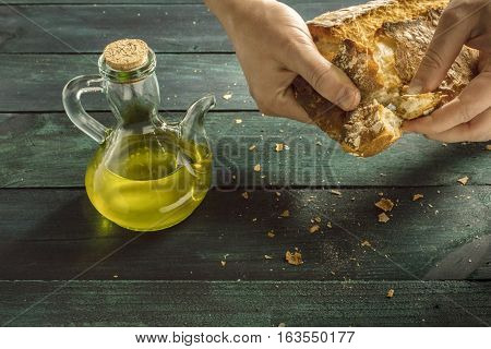 A candid photo of a pitcher of olive oil on a wooden board, with a man's hand tearing off a piece from a loaf of bread, with copyspace