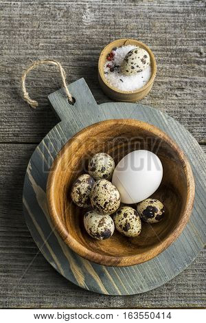 Quail eggs in a wooden bowl on a cutting board on a dark background with salt. Top view