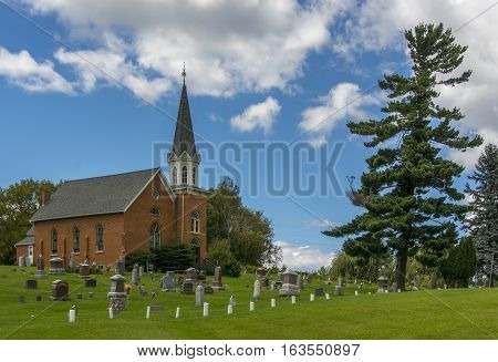 A beautiful brick country church standing on a hill along a rural Wisconsin road with a stately pine and a cemetery.