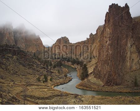 Fog lays over the rocky formations paths trees and Crooked River at Smith Rocks State Park in Central Oregon on a winter day.