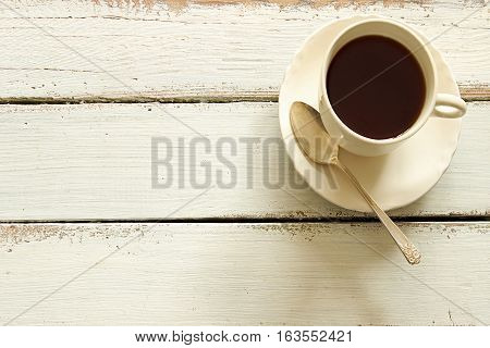 Coffee and vintage teaspoon against white wood background. Room for copy.
