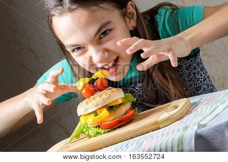 11 year old caucasian girl runs at on a burger to eat it. Hamburger in the form faces of tomatoes as eyes and bread with lettuce leaf in the form of a mouth. Diagonal composition close up portrait.
