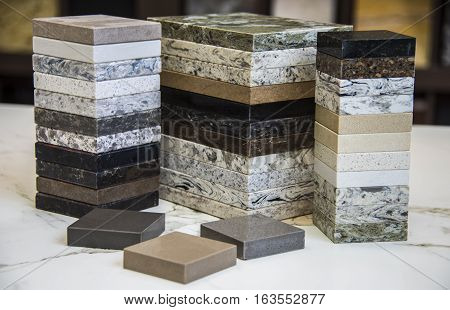 3 stacks of different counter top samples for kitchen and baths, with more blurred counter top samples in the background.