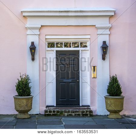 The doorway or entrance to a historic home with gas lights on either side and an old brass door knocker.