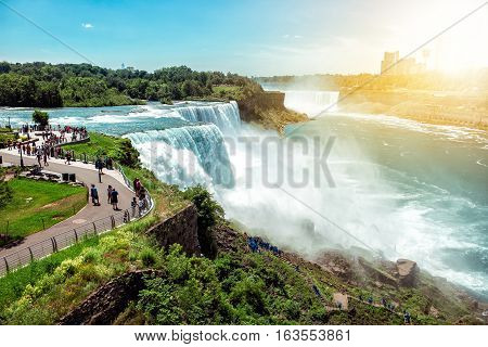 American side of Niagara falls NY USA. Tourists enjoying beautiful view to Niagara Falls during hot sunny summer day.