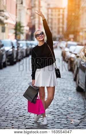 Beautiful fashionable young woman with shopping bags walking on city street and having fun. Happy girl enjoy shopping time durig the trip.