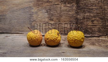 Three shriveled  old yellow apples. Wooden background