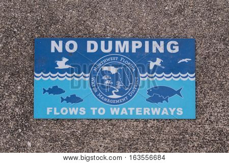 November 13, 2016: Apalachicola, United States. No Dumping Sign in Sidewalk reminds people to protect the local water