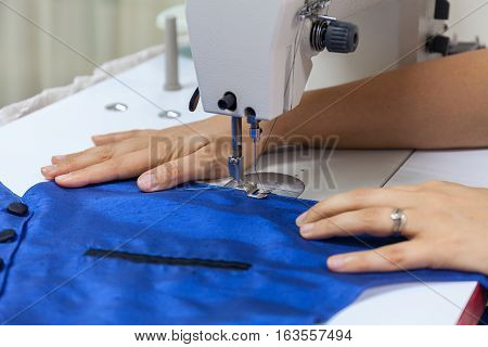 Tailoring Process - Women's hands behind her sewing blue stock photo