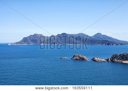 View across the ocean towards a mountain range in the Freycinet National Park on the east coast of Tasmania Australia