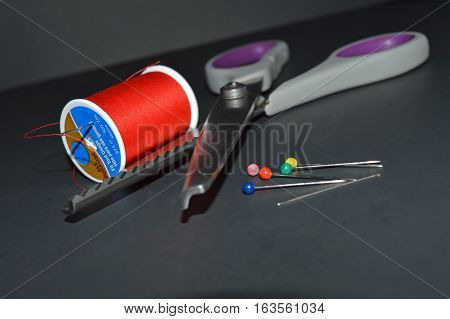 Thread needle pins and pinking shears on black background