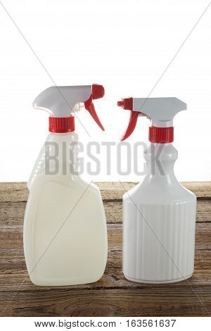 Plastic Spray Bottles on a Wooden Background