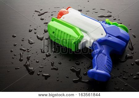 Plastic Toy Water Pistol on Wooden Background