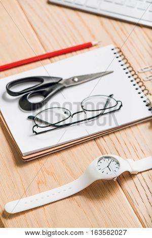 Shears, eyewear are on notebook beside white wristwatch
