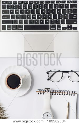 Open laptop is near cup of coffee, eyewear and notebook with wristwatch. Top view