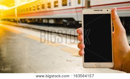 Hand holding blank smartphone screen for text with train station or railway station for background.