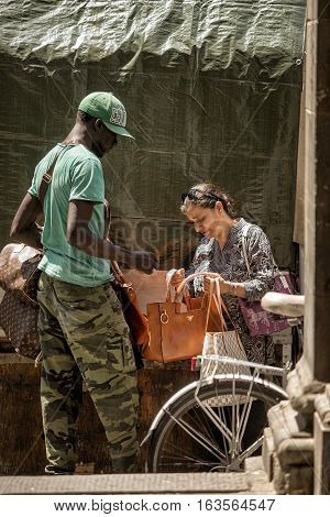 Florence Italy-June 10 2015. Street vendor trying to sell fashion handbags to a woman on the streets of Florence Italy