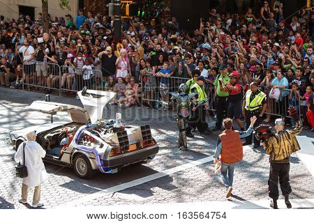 ATLANTA, GA - SEPTEMBER 2016: The famous Delorean car and characters from the Back to the Future movies wave as they walk past a huge crowd of spectators along the Dragon Con parade route on Peachtree Street in Atlanta GA on September 3 2016.