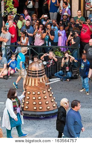 ATLANTA, GA - SEPTEMBER 2016:  A crowd of spectators watches and takes pictures with smart phones as a robot character passes by in the annual Dragon Con parade on Peachtree Street in downtown Atlanta in Atlanta GA on September 3 2016.