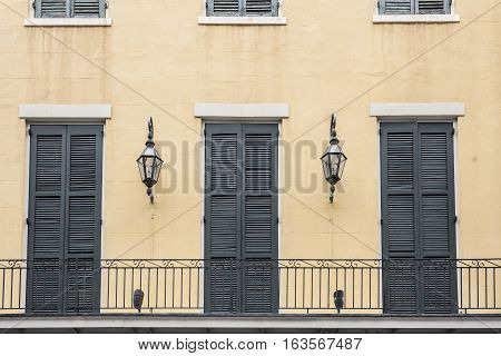 Balcony of a French Quarter (New Orleans Louisiana) apartment with doors and gas lamps.