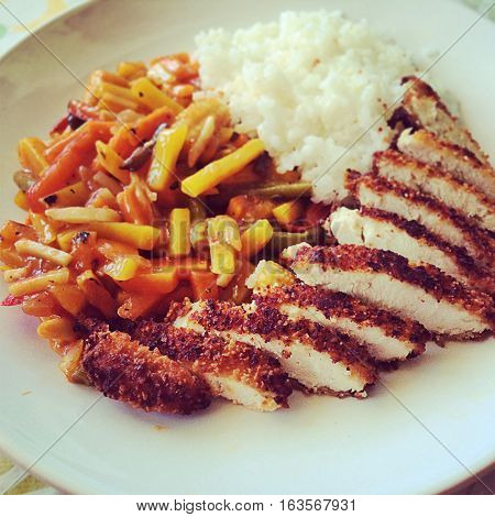 chicken chop with rice and garnish on a plate