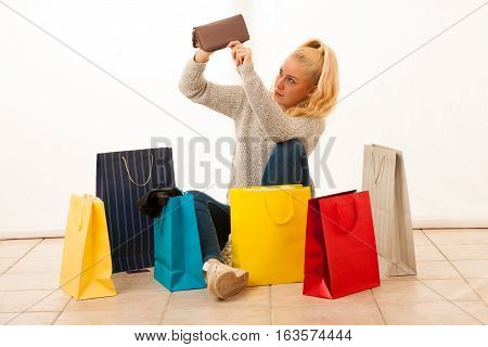 angry young woman siting on flor after shopping checking empty wallet