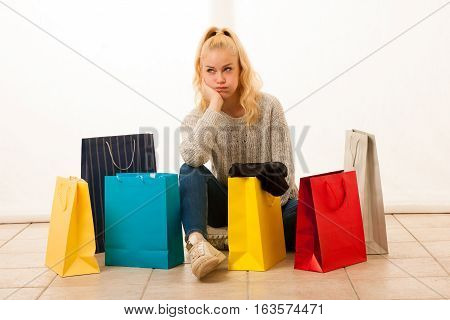 woman with shopping bags after shopping siting on flor