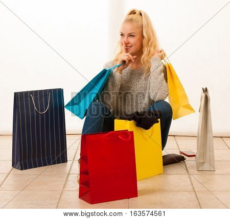 Happy woman checking bags after shopping siting on flor