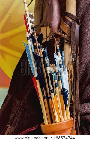 Historical set of old wooden arrows with bright plumage in the quiver on human back closeup