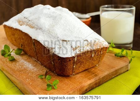 Freshly baked homemade fruitcake decorating the top with powdered sugar on a cutting board with a glass of milk.