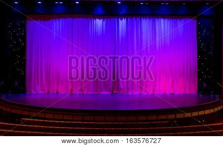 Stage with Purple Curtains in dark theater