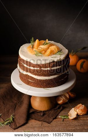 The chocolate cake with clementines and rosemary on cakestand on wooden background. Still life.