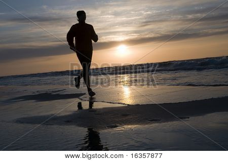 Beautifull woman running on the beach at sunset