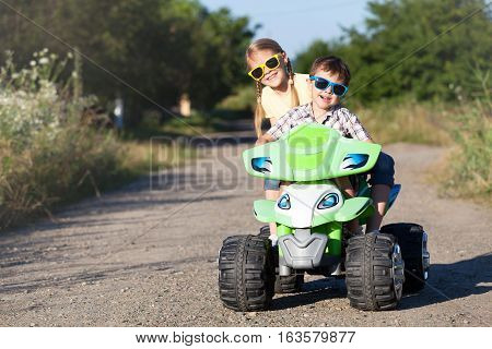 Happy little children playing on road at the day time. They driving on quad bike in the park. Kids having fun on the nature. Concept of happiness.