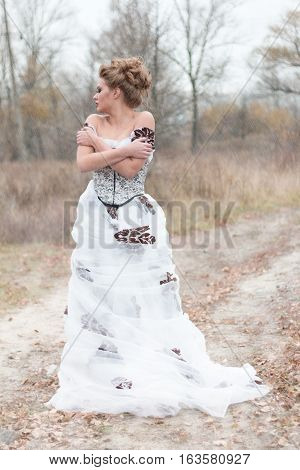 Beautiful young lady in gorgeous vintage white dress. Late autumn cold. Melancholy.