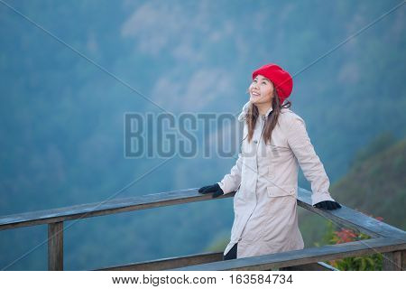 Young woman on a cliff overlooking the mountains with fog Thailand