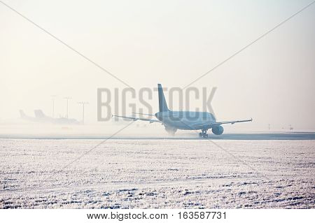 Airport in winter. Airplane is taking off in frosty day.