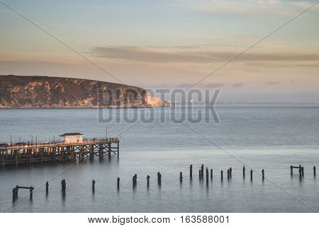 Beautiful Landscape Image Of Colorful Sunrise Over Ocean And Derelict Pier In Distance