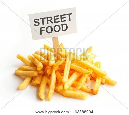 Pile of potato fries on kraft paper. Poor street food, obesity, heart disease. French fries with a sign, Empty copy space for text