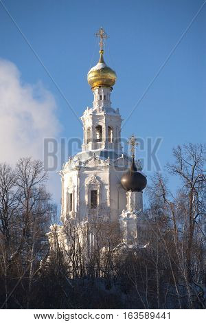 Top of Russian country church with golden cupola over blue sky in winter season