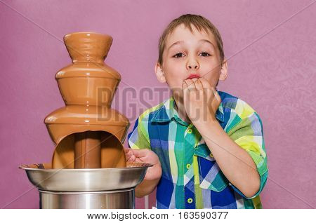 boy tastes the chocolate from the chocolate fountain