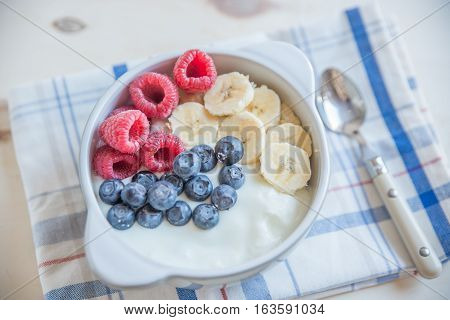 Healthy Yogurt with fresh fruit on a table