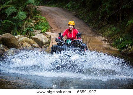 The girl driving an ATV through the river Spree.