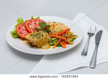 Chicken with rice and vegetables on white plate fork knife stock photo