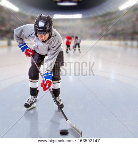 Boy hockey player handling puck on ice with arena full of fans in the stands and copy space. 3D rendering of hockey rink arena.